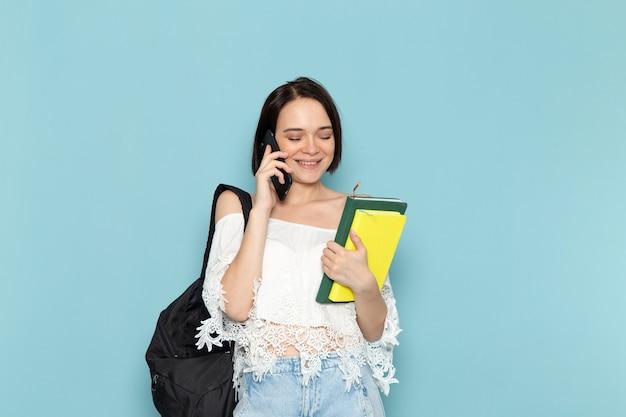 Vooraanzicht jonge vrouwelijke student in wit overhemd, spijkerbroek en zwarte tas met voorbeeldenboeken praten aan de telefoon op de blauwe ruimte vrouwelijke student universiteit onderwijzen