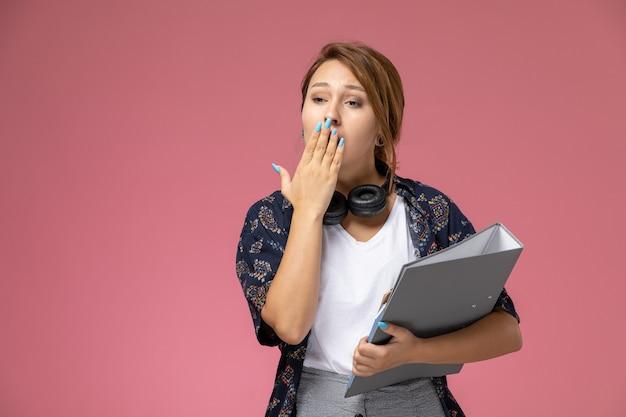 Vooraanzicht jonge vrouwelijke student in wit t-shirt en grijze broek geeuwen op roze achtergrond student lessen hogeschool