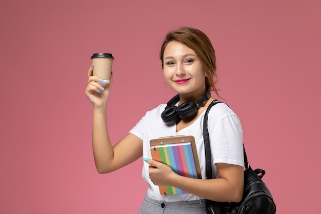 Vooraanzicht jonge vrouwelijke student in wit t-shirt met beurt en tas poseren en houden koffiekopje op roze achtergrond les universiteit college studieboek