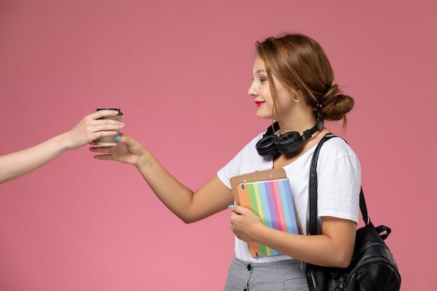 Vooraanzicht jonge vrouwelijke student in wit t-shirt met beurt en tas poseren en nemen koffiekopje op de roze achtergrond les university college studieboek
