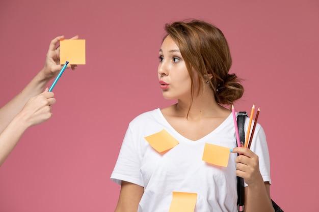 Vooraanzicht jonge vrouwelijke student in wit t-shirt met potloden en poseren op de roze achtergrond lessen hogeschool studie