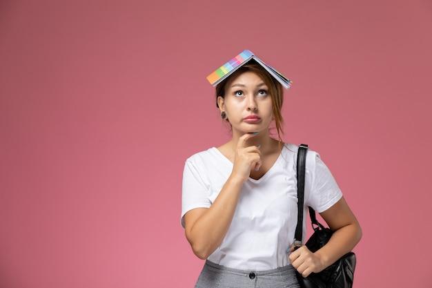 Vooraanzicht jonge vrouwelijke student in wit t-shirt met voorbeeldenboek en tas poseren en denken op roze achtergrond les universiteit college studieboek