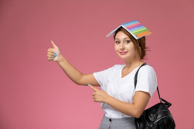 Vooraanzicht jonge vrouwelijke student in wit t-shirt met voorbeeldenboek en tas poseren en glimlachend op roze achtergrond les universiteit college studieboek