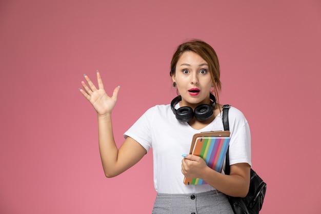 Vooraanzicht jonge vrouwelijke student in wit t-shirt met voorbeeldenboek oortelefoons en tas poseren op roze achtergrond lessen universiteit college studieboek