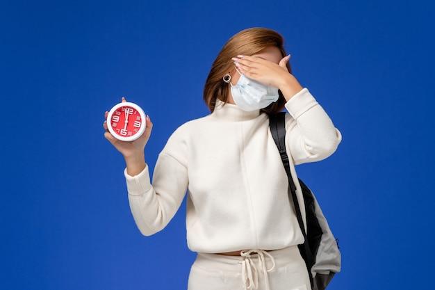 Vooraanzicht jonge vrouwelijke student in witte trui die masker draagt en klok op de blauwe muur houdt