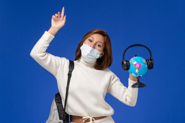 Vooraanzicht jonge vrouwelijke student in witte trui dragen masker en rugzak met globe met koptelefoon op de blauwe muur