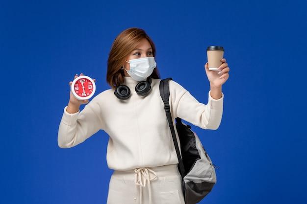 Vooraanzicht jonge vrouwelijke student in witte trui dragen masker en rugzak met koffie en klok op de blauwe muur