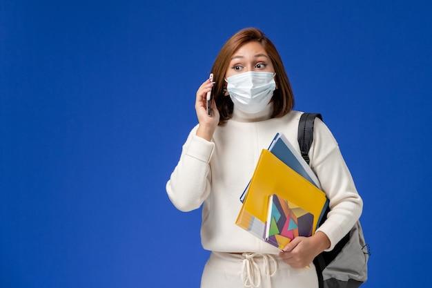 Vooraanzicht jonge vrouwelijke student in witte trui dragen masker met tas en voorbeeldenboeken praten aan de telefoon op blauwe muur