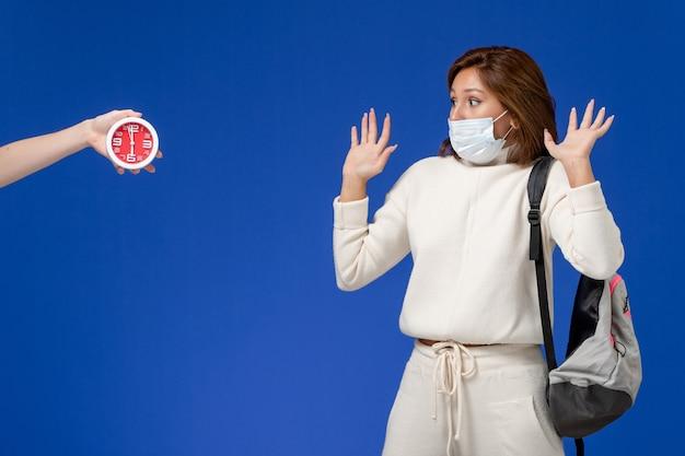 Vooraanzicht jonge vrouwelijke student in witte trui met masker bang voor vrouw met klok op blauwe muur