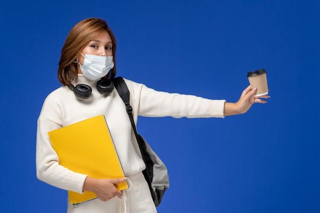 Vooraanzicht jonge vrouwelijke student in witte trui met masker en rugzak met bestanden en koffie op het blauwe bureau college universiteit boek lessen