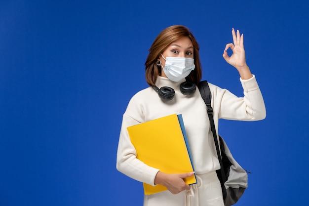 Vooraanzicht jonge vrouwelijke student in witte trui met masker en rugzak met bestanden op de blauwe muur