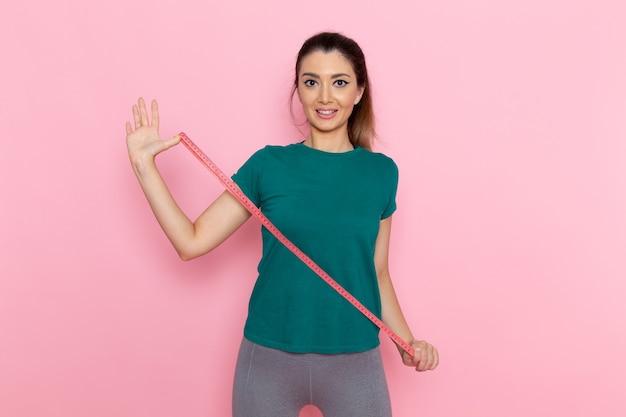Vooraanzicht jonge vrouwelijke taille maatregel op de roze muur schoonheid sport oefening atleet training slank