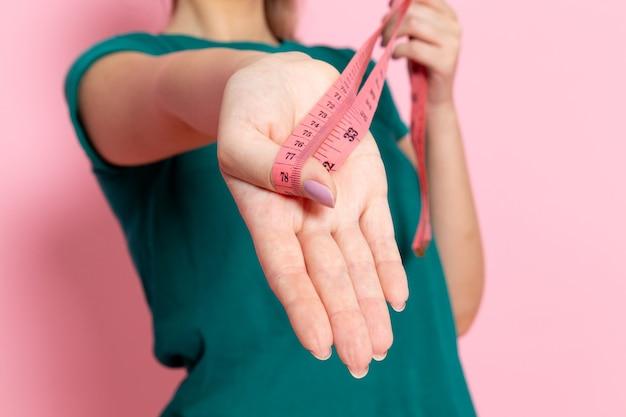 Vooraanzicht jonge vrouwelijke taille maatregel op de roze muur schoonheid sport oefening atleet trainingen slank