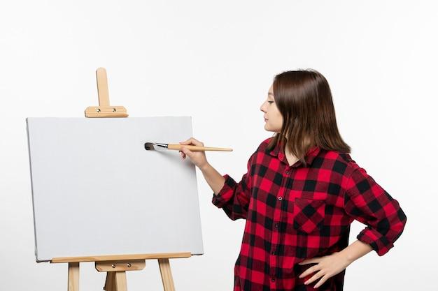 Vooraanzicht jonge vrouwelijke tekening met kwast op ezel op witte muur