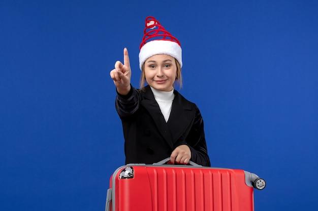 Vooraanzicht jonge vrouwelijke tellen met nummer op blauwe muur vakantie vakantie vrouw