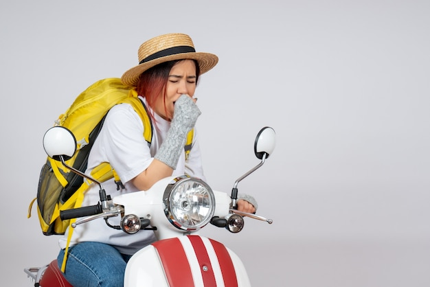 Vooraanzicht jonge vrouwelijke toerist zittend op motorfiets hoesten op witte muur voertuig vrouw snelheid foto rit toerist