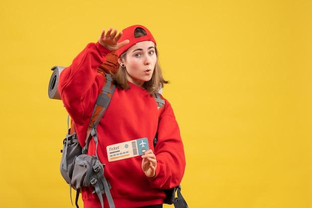 Vooraanzicht jonge vrouwelijke wandelaar met het vliegticket van de rugzakholding
