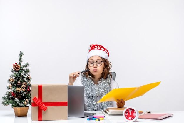 Vooraanzicht jonge vrouwelijke werknemer vóór haar plaats zitten en werken met documenten op witte achtergrond