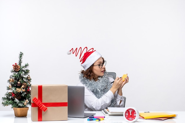 Vooraanzicht jonge vrouwelijke werknemer zit voor haar plaats schrijven van notities op witte achtergrond