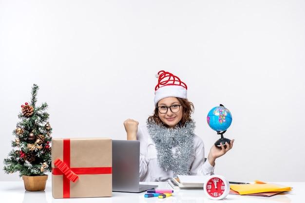 Vooraanzicht jonge vrouwelijke werknemer zittend vóór haar plaats met aardebol op wit bureau