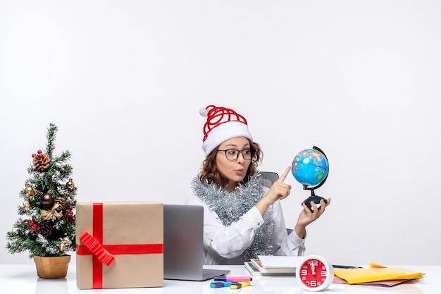 Vooraanzicht jonge vrouwelijke werknemer zittend vóór haar plaats met earth globe op witte achtergrond