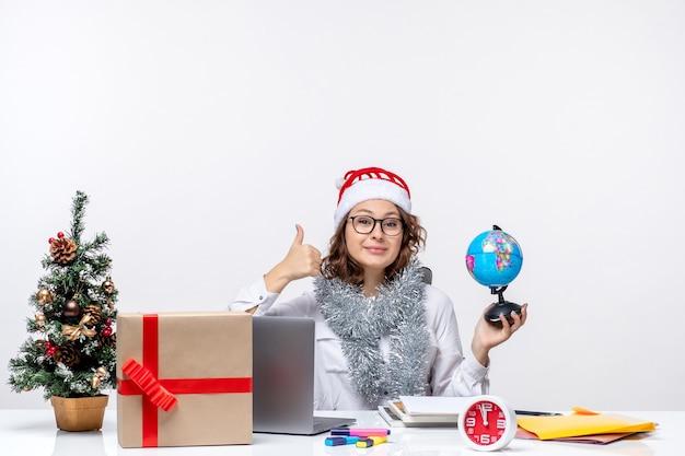 Vooraanzicht jonge vrouwelijke werknemer zittend voor haar plaats met earth globe op witte vloer kantoor werk kerstbaan dame