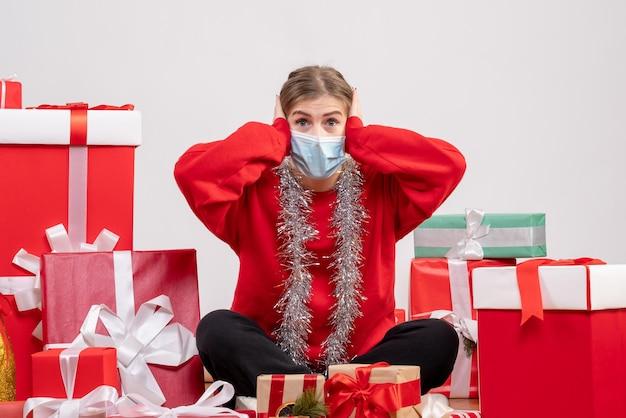 Vooraanzicht jonge vrouwelijke zitten met kerstcadeautjes in masker
