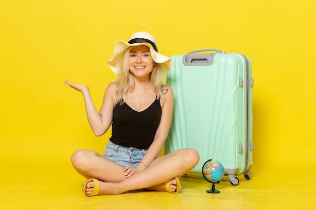Vooraanzicht jonge vrouwelijke zittend met haar tas op gele muur reis vakantiereis zeereis zon