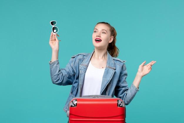 Vooraanzicht jonge vrouwelijke zonnebril houden en voorbereiden op vakantie op de blauwe ruimte