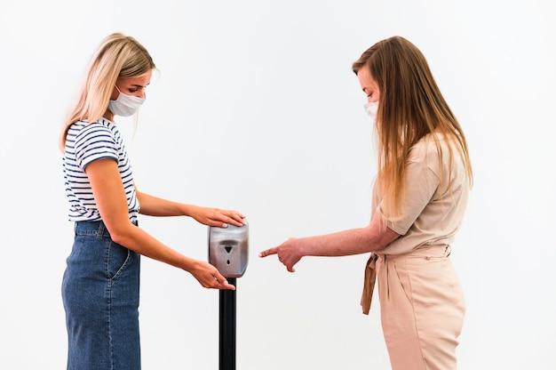 Vooraanzicht jonge vrouwen die handen desinfecteren