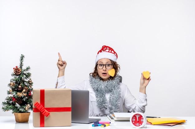 Vooraanzicht jonge werkneemster zittend vóór haar plaats met stickers op witte achtergrond