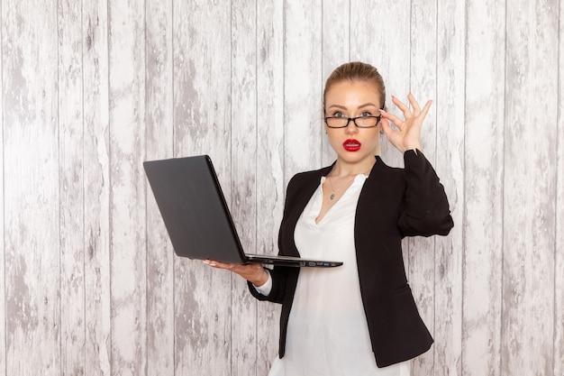 Vooraanzicht jonge zakenvrouw in strikte kleding zwarte jas met behulp van laptop op witte muur werk baan kantoor bedrijf