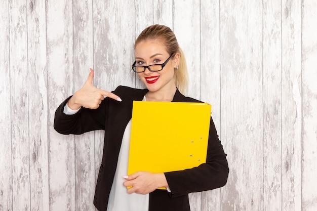 Vooraanzicht jonge zakenvrouw in strikte kleding zwarte jas met bestanden en documenten lachend op wit oppervlak