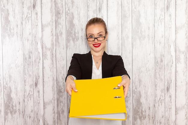 Vooraanzicht jonge zakenvrouw in strikte kleding zwarte jas met bestanden en documenten op het licht-witte oppervlak