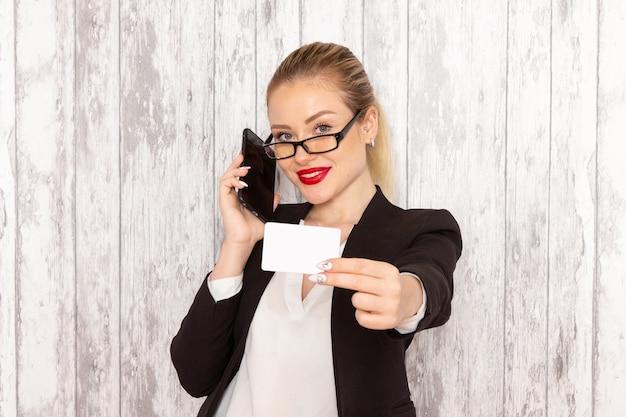 Vooraanzicht jonge zakenvrouw in strikte kleding zwarte jas met kaart en telefoon op wit bureau