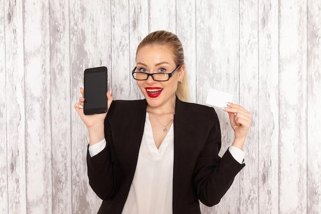 Vooraanzicht jonge zakenvrouw in strikte kleding zwarte jas met kaart en telefoon op wit oppervlak