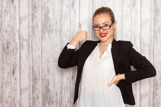 Vooraanzicht jonge zakenvrouw in strikte kleding zwarte jas met optische zonnebril glimlachend op witte muur werk job kantoor vrouwelijke zakelijke bijeenkomst
