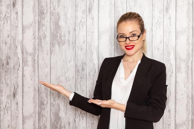 Vooraanzicht jonge zakenvrouw in strikte kleding zwarte jas met optische zonnebril glimlachend op witte muur werk job kantoor vrouwelijke zakelijke bijeenkomsten