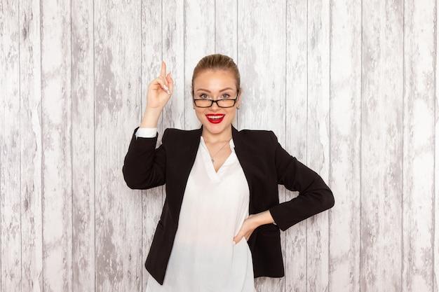 Vooraanzicht jonge zakenvrouw in strikte kleding zwarte jas met optische zonnebril lachend op wit bureau werk baan kantoor zakelijke vrouw dame
