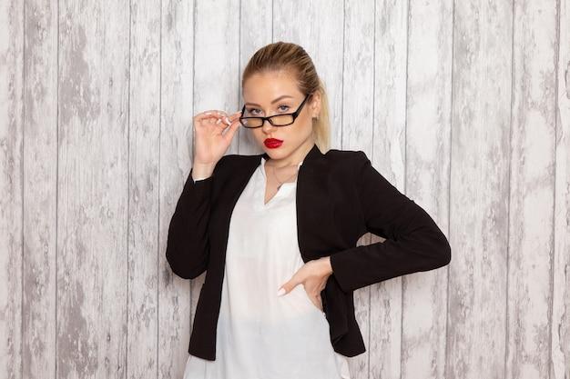 Vooraanzicht jonge zakenvrouw in strikte kleding zwarte jas met optische zonnebril op witte muur werk job kantoor vrouwelijke zakelijke bijeenkomsten