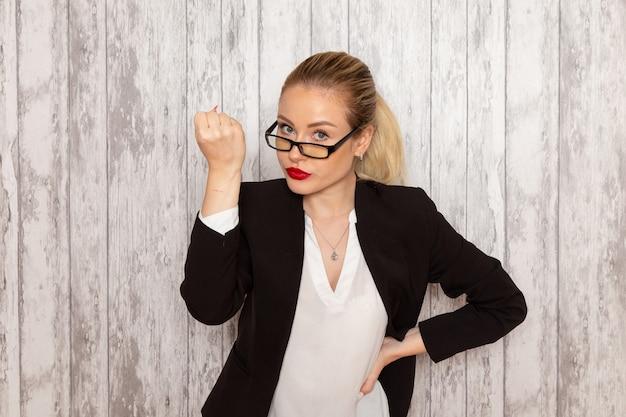 Vooraanzicht jonge zakenvrouw in strikte kleding zwarte jas met optische zonnebril poseren bedreigend op witte muur werk job kantoor vrouwelijke bedrijf
