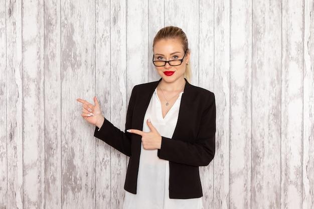 Vooraanzicht jonge zakenvrouw in strikte kleding zwarte jas met optische zonnebril poseren en lachend op witte muur job office vrouwelijke bedrijf