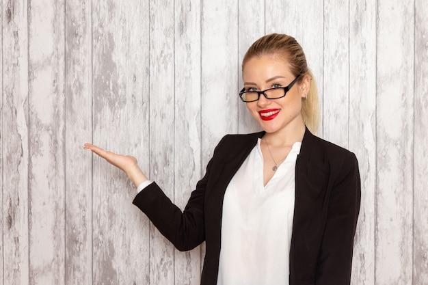Vooraanzicht jonge zakenvrouw in strikte kleding zwarte jas met optische zonnebril poseren en lachend op witte muur werk job kantoor vrouwelijke bedrijf