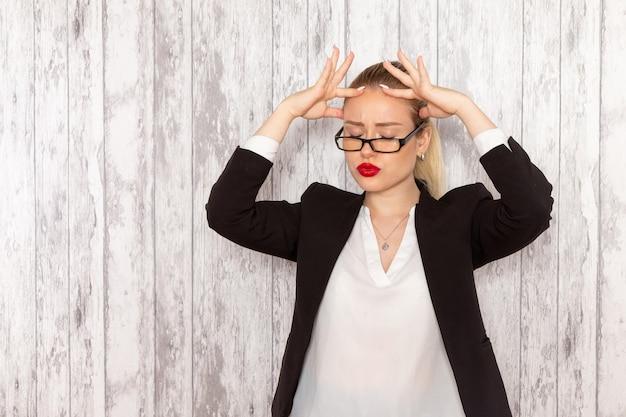 Vooraanzicht jonge zakenvrouw in strikte kleding zwarte jas met optische zonnebril poseren gestrest op witte muur werk job kantoor bedrijf