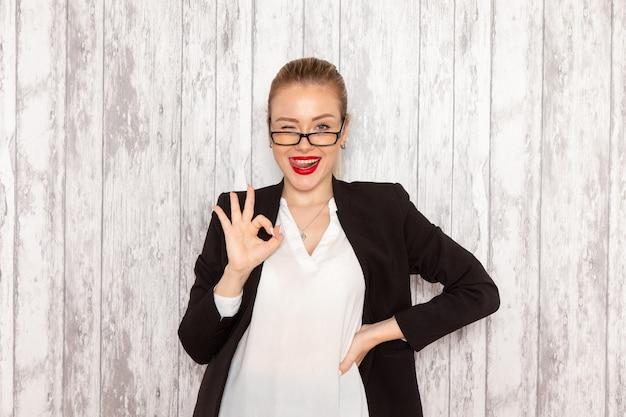 Vooraanzicht jonge zakenvrouw in strikte kleding zwarte jas met optische zonnebril poseren op grijs witte muur werk job kantoor zakenvrouw dame