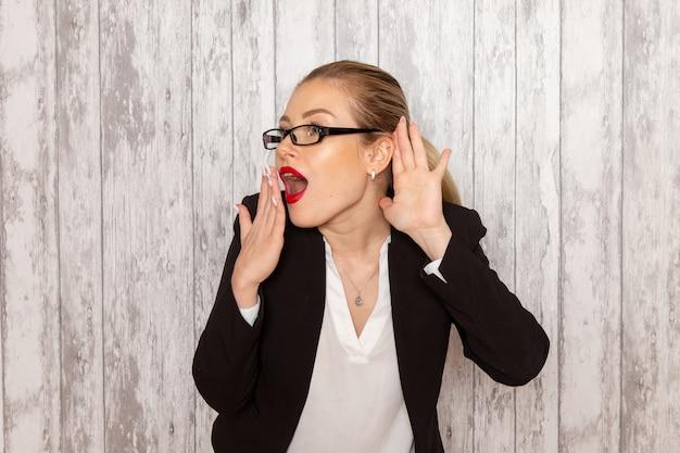 Vooraanzicht jonge zakenvrouw in strikte kleding zwarte jas met optische zonnebril probeert te horen op wit bureau werk job office vrouwelijke bedrijf