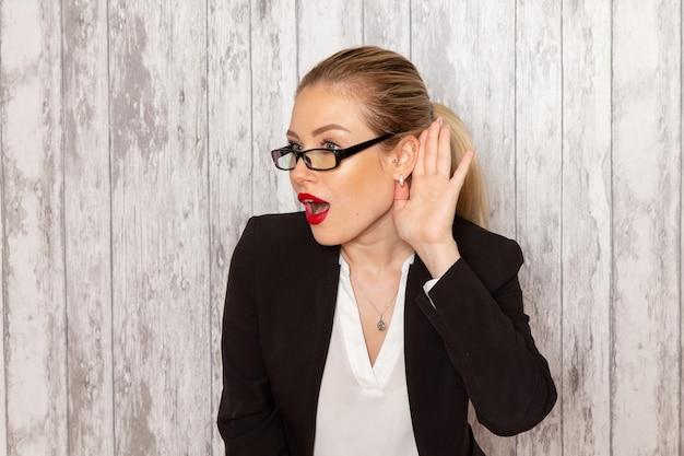 Vooraanzicht jonge zakenvrouw in strikte kleding zwarte jas met optische zonnebril proberen te horen op witte muur werk job kantoor vrouwelijke bedrijf