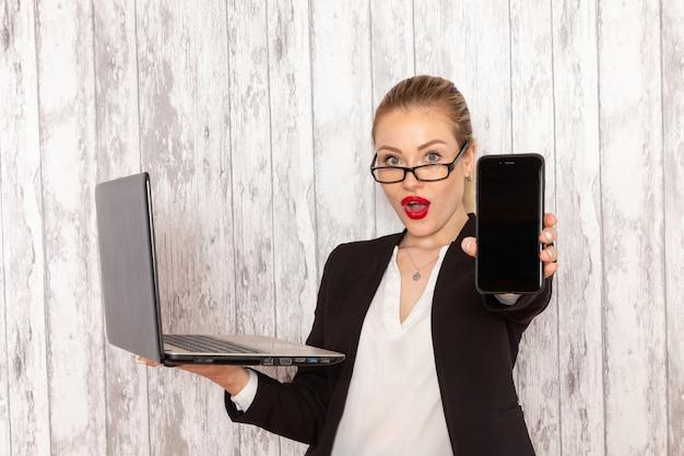 Vooraanzicht jonge zakenvrouw in strikte kleren zwarte jas met behulp van haar laptop en telefoon bedrijf op wit oppervlak