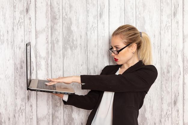Vooraanzicht jonge zakenvrouw in strikte kleren zwarte jas met behulp van haar laptop op wit oppervlak