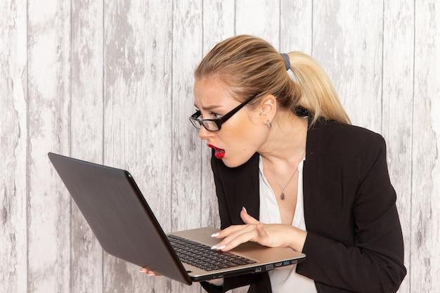 Vooraanzicht jonge zakenvrouw in strikte kleren zwarte jas met behulp van laptop op het witte bureau werk baan kantoor zakelijke werknemer vrouw